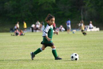 Meisje speelt voetbal, kost een kind