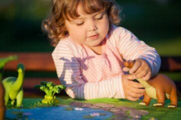 Hoogbegaafd meisje speelt met dinosaurussen