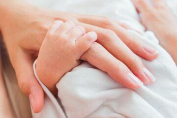 Moeder met sinustrombose houdt hand vast baby