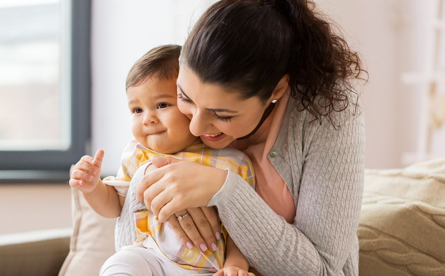 Moeder knuffelt liefdevol peuter bij opvoeding
