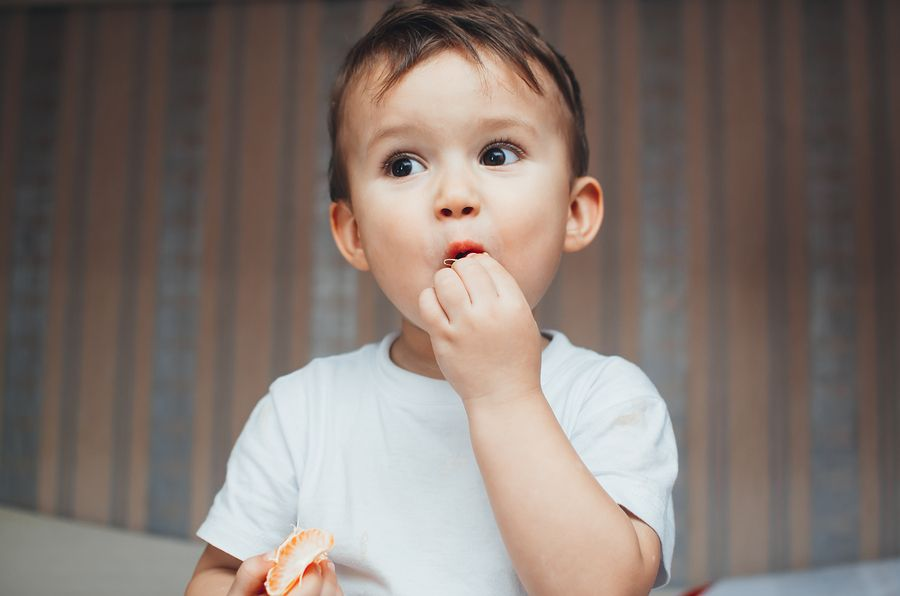 Peuter snoept van gezonde snack: een mandarijntje