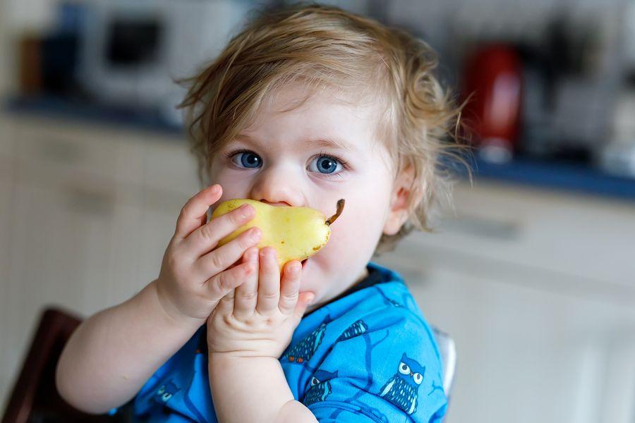 gezonde peuter eet een peer