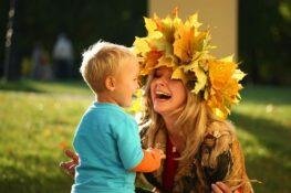 Moeder en peuter spelen met bladeren in vrije tijd