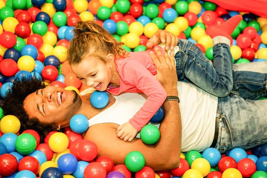 Vader speelt met dochter in een binnenspeeltuin in de ballenbak