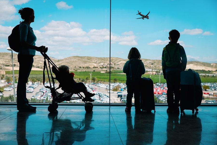 Moeder met 3 kinderen op vliegveld