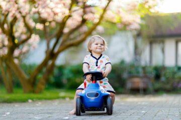 Meisje op blauwe loopauto