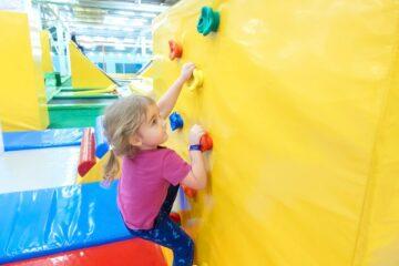 Meisje klimt op kinderklimmuur in binnenspeeltuin
