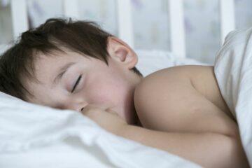 peuter slaapt met dekbed en kussen