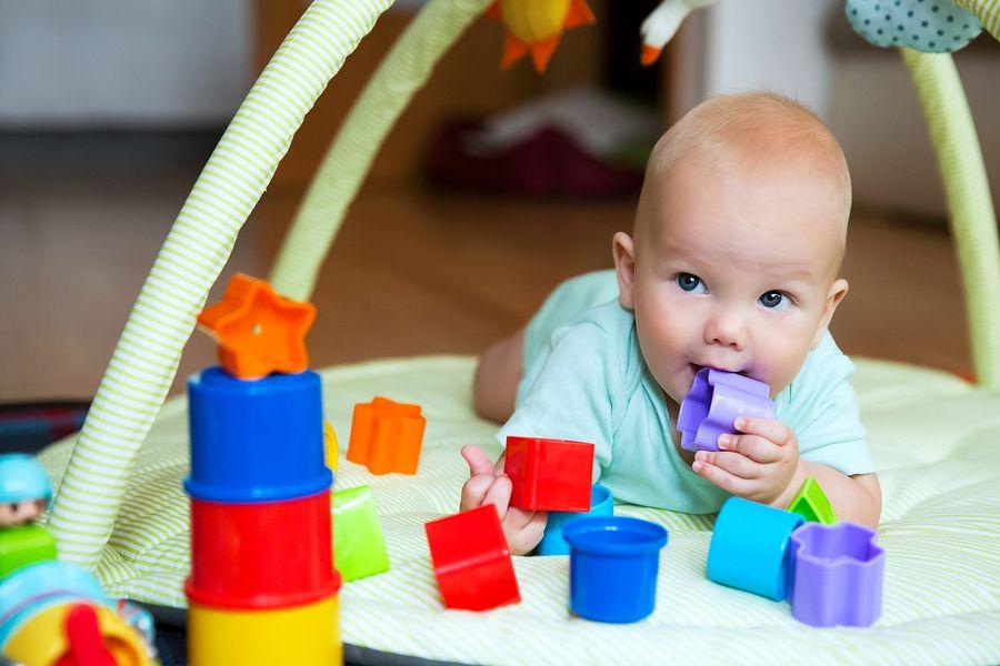 Baby ontdekt blokje door het in zijn mond te stoppen
