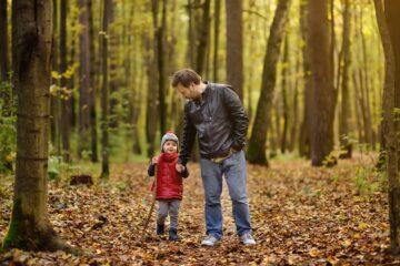 Vader en peuter maken een boswandeling
