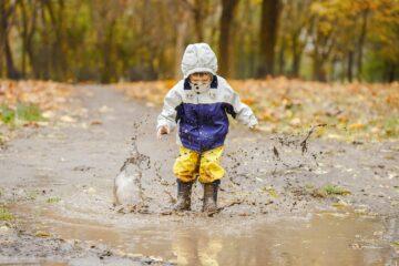 Peuter is aan het buitenspelen en springt in de modder