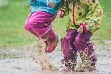 Peuters zijn aan het buitenspelen en springen in regenplassen