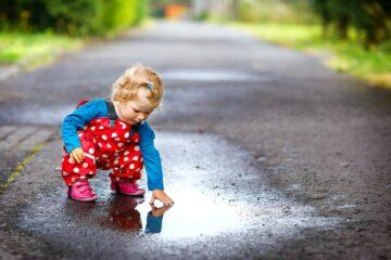 Peuter is aan het buitenspelen en verft met regen en modder
