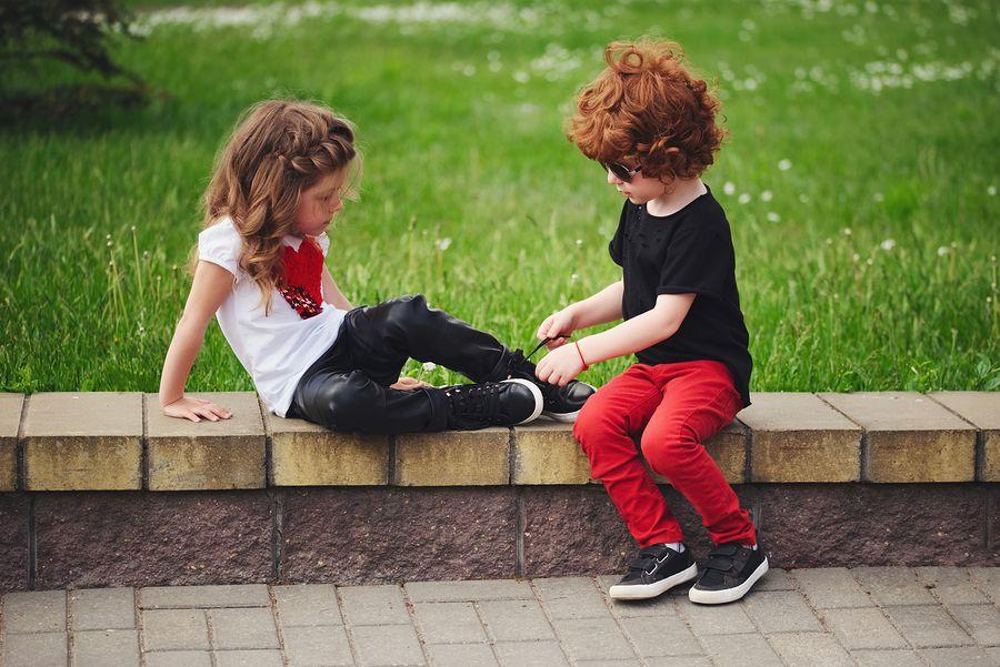 Klein jongetje helpt klein meisje met veters strikken