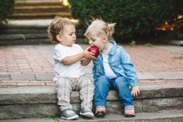 twee peuters leren delen door appel samen te eten