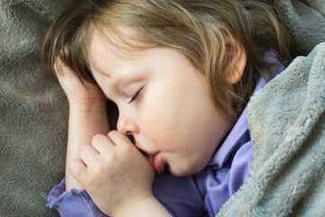 Peuter slaapt met duim in mond, bezig met duimen afleren