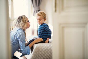 Moeder praat in de slaapkamer met peuter over de dood