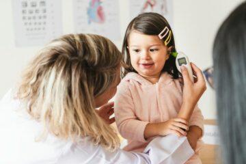 dokter meet temperatuur met oorthermometer bij meisje