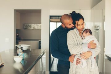 Ouders staan in keuken met pasgeboren baby te knuffelen op eerste dag thuis