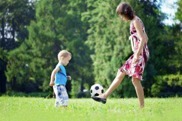 Peuter en moeder spelen samen buiten met de voetbal