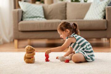 Peuter speelt met beer en theeserviesje, speelgoed voor peuter van 3 jaar