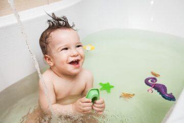Peuter speelt met speelgoed voor peuter van 3 jaar in bad