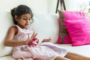 Meisje knipt met kinderschaar als peuterspelletje