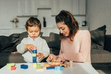 Moeder en zoon bouwen toren als peuterspelletje