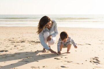 Moeder en peuter verzamelen schelpen op strand als peuterspelletje
