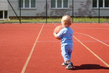 Peuter speelt het peuterspelletje basketbal