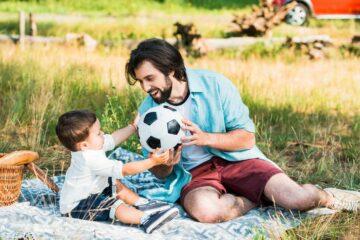 Vader en zoontje gooien over met de bal als peuterspelletje