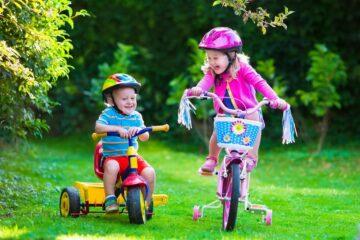 Peuter speelt op driewieler met bak, samen met oudere zus op kinderfiets met zijwieltjes