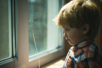 Peuterjongetje kijkt verdrietig naar buiten na echtscheiding ouders