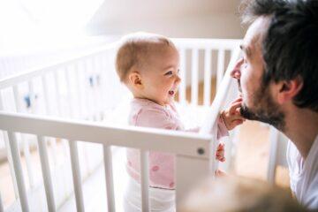 Meisje is vroeg wakker en raakt papa's baard aan vanuit haar bedje