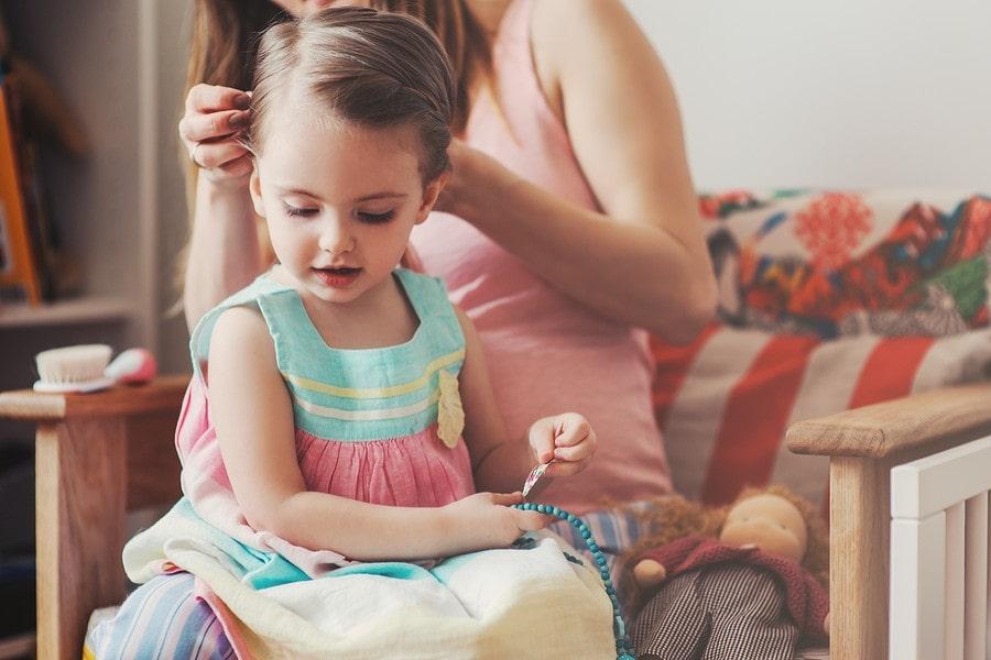 Moeder controleert kind op luizen