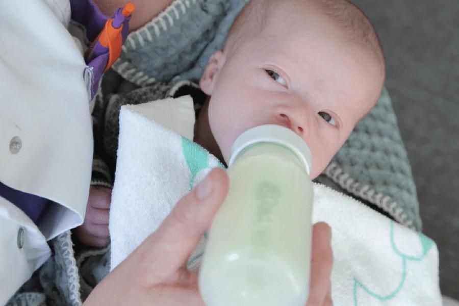 Kraamverzorgende geeft baby de fles
