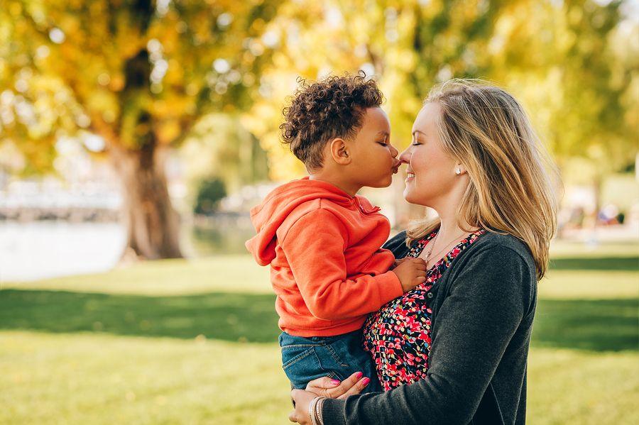 Moeder knuffelt buiten met haar peuter van 3 jaar