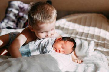 Peuter knuffelt met zijn nieuw zusje en is niet jaloers