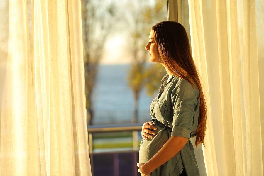 Zwangere vrouw met bevalangst staart droevig uit het raam