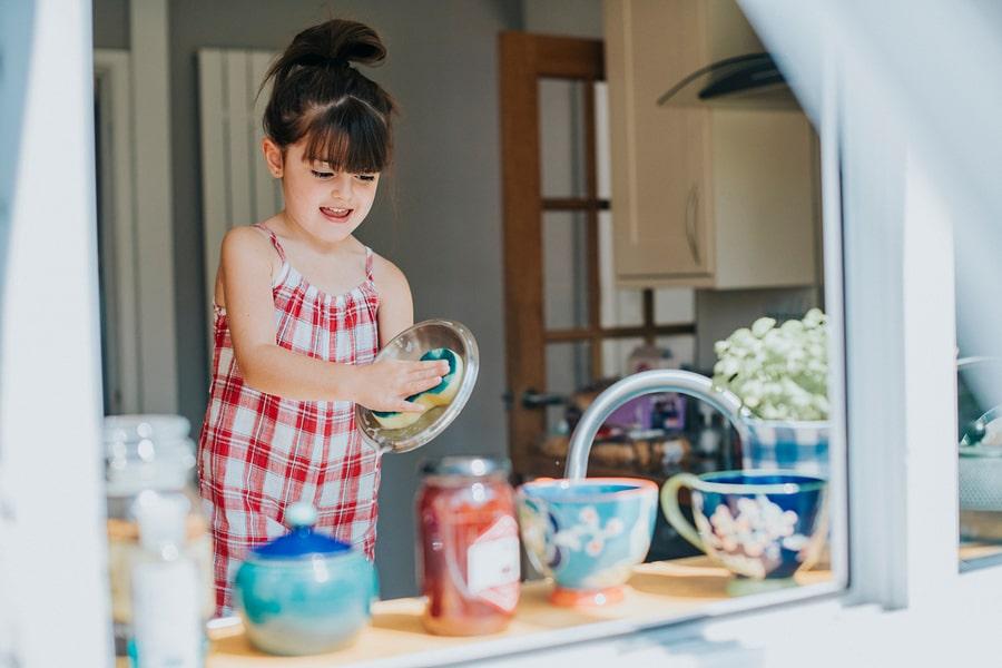 Meisje van 3 jaar doet de afwas