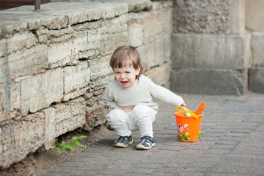 Kind van 3 jaar zit op de grond met een driftbui