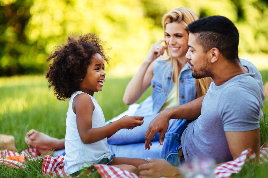 Kind van 3,5 jaar zit lachend met ouders in het park
