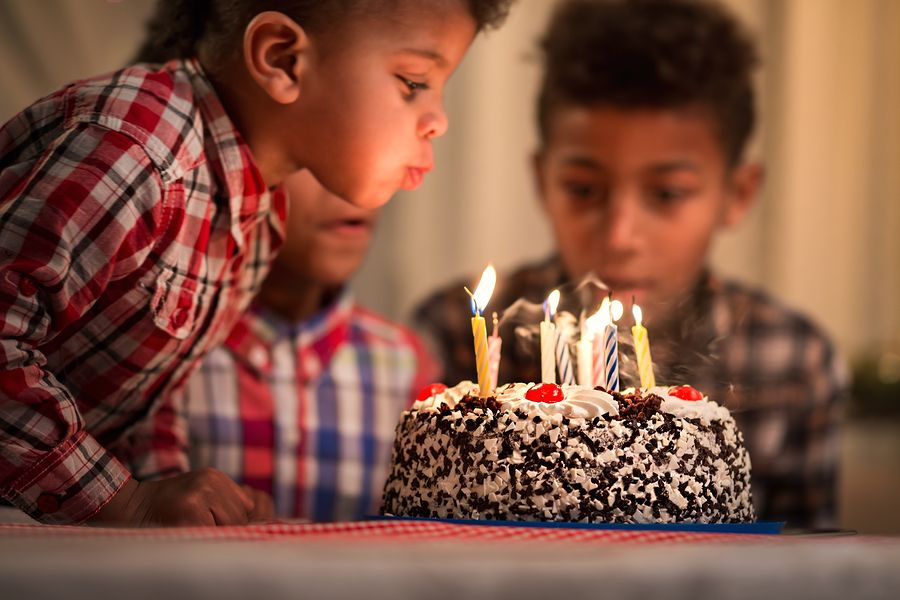 Peuter van 4 jaar oud blaast kaarsjes op verjaardagstaart uit