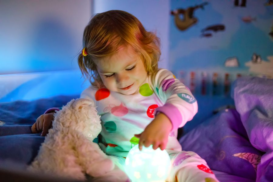 Kindje speelt met nachtlampje die als slaaptrainer gebruikt wordt