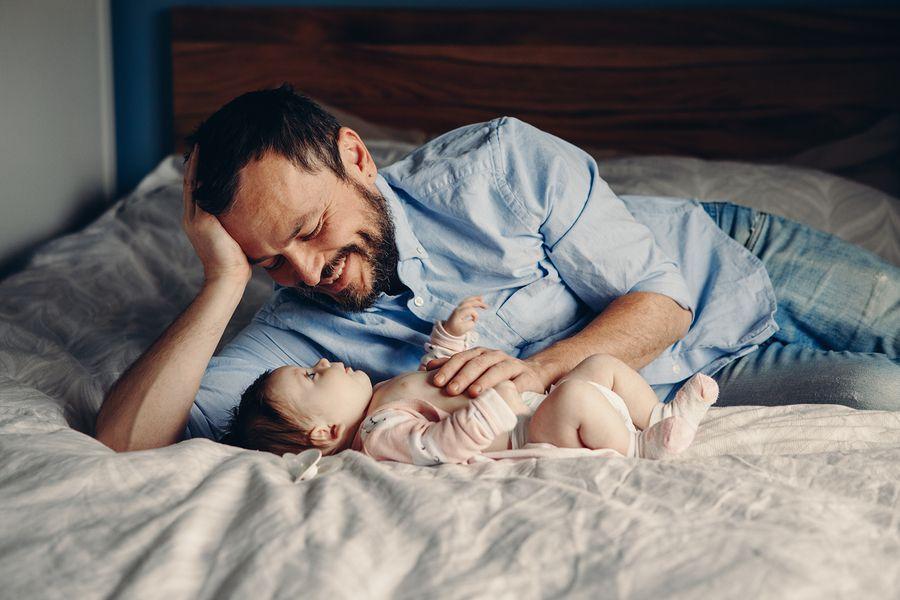 Dankzij de WIEG wet geniet een vader op bed van tijd met zijn pasgeboren baby