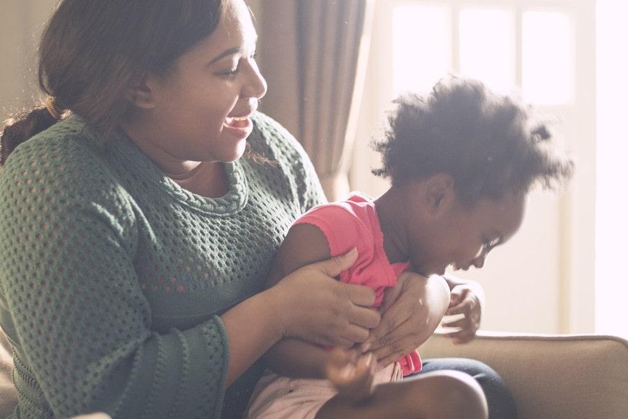 Kind van 2,5 jaar zit lachend bij moeder op schoot