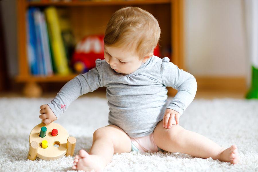 baby speelt met speelgoed voor motorische ontwikkeling