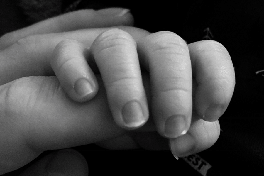 Moeder houdt handje van pasgeboren baby vast als onderdeel van haar bevallingsverhaal