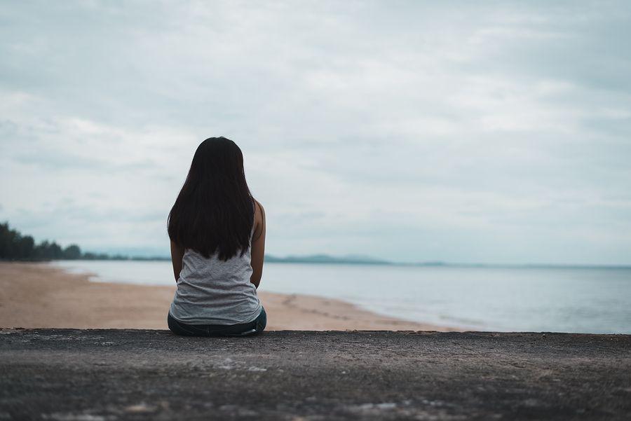 Vrouw zit op het strand in haar eentje