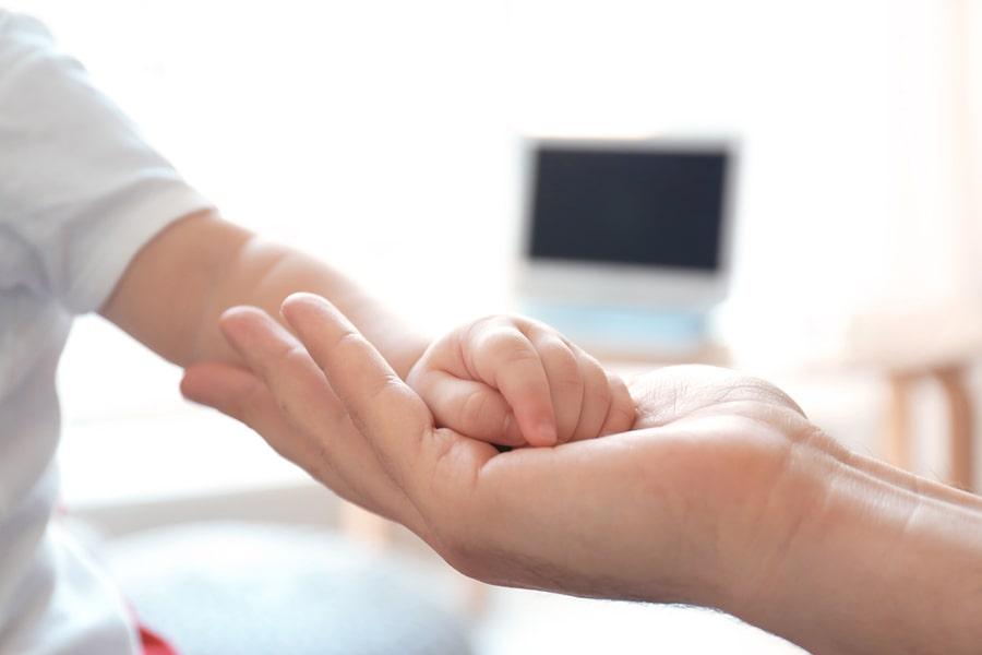 Moeder houd hand vast van peuter die klaar is voor operatie